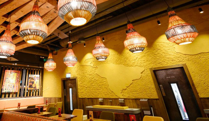 """Carved clay """"world map"""" finish. Nando's restaurant in Gatwick, South Terminal. Courtesy of Nando's"""