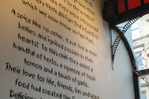 Carved clay text wall, Nando's restaurant in Glasgow